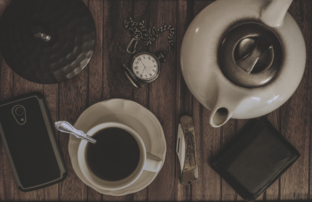 billfold: Coffee Tea Pot, Cup And Saucer, Pocket Knife And Watch, Wallet And Cell Phone On A Wood Table. Stock Photo