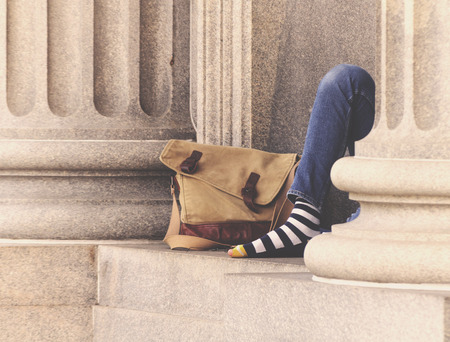 Homeless Man On Street Sitting Next To Building With Striped Socks And Bag