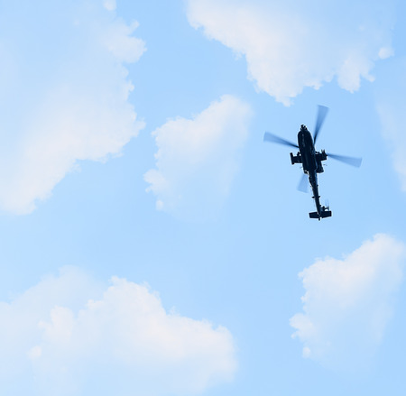 Military Helicopter Flying Above In Blue Cloudy Sky Stock Photo
