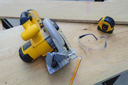 Power Circular Saw And Tape Measure Lying On Plywood