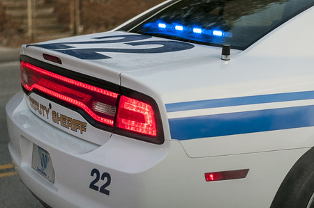 Back Section Of Police Car With Flashing Blue Lights During Traffic Stop