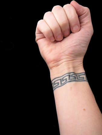 body art: Fist Over Wrist Tattoo Body Art of Greek Key Symbol isolated on black background Stock Photo