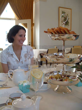 high tea: Young woman smiling at proper tea service