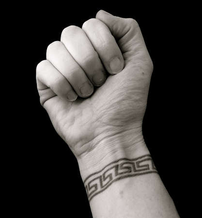 Fist with Wrist Tattoo Body Art in Greek Key Pattern over Black Background photo