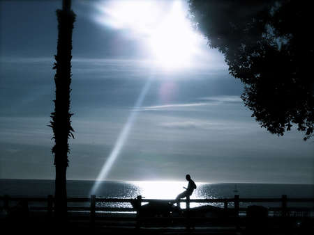 Silhouette of Man by the sea at sunset photo