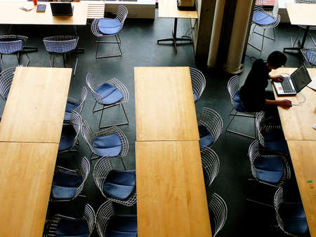 cafeterias: Man on laptop computer in university building, seen from above Stock Photo