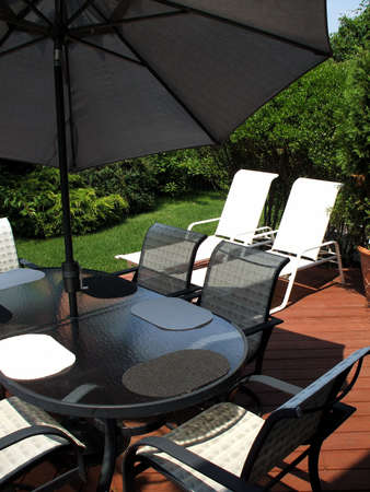 Suburban home backyard with patio furniture and umbrella