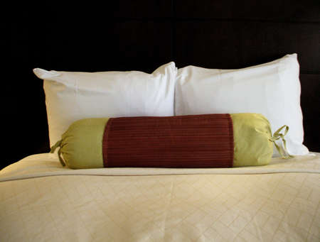 Simple and inviting bed with colorful accent pillow Stock Photo - 1090989