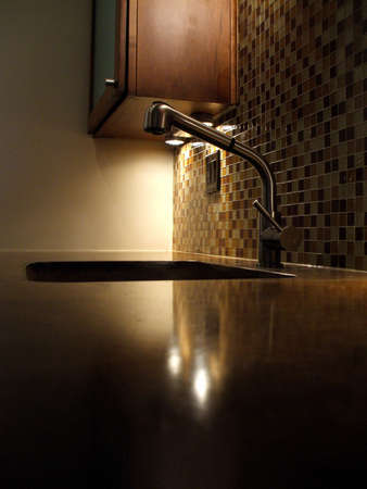 Elegant Home Kitchen with Poured Concrete Counter and Sink Stainless Steel Faucet and Glass Tiles