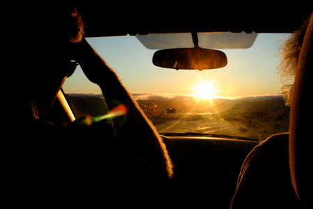 A man and woman drive their car into the sunset Stock Photo