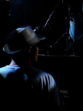 lounge: Young man in hat at music concert standing by stage Stock Photo