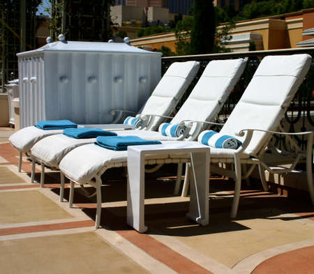 lounge: Three White Lounge Chairs Sitting Empty by the Swimming Pool
