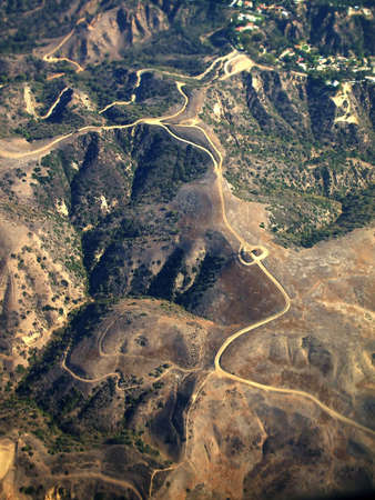 Aerial view of single winding road and rotary running through rural mountain landscape