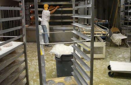 Baker lugares masa de pan en horno industrial en Gourmet Bakery  Foto de archivo - 1991463