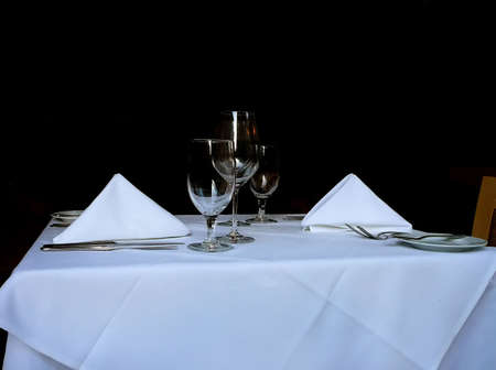 Traditional Table Place Setting in Restaurant Including Silverware, Wine Glasses, and Cloth Napkins Stock Photo