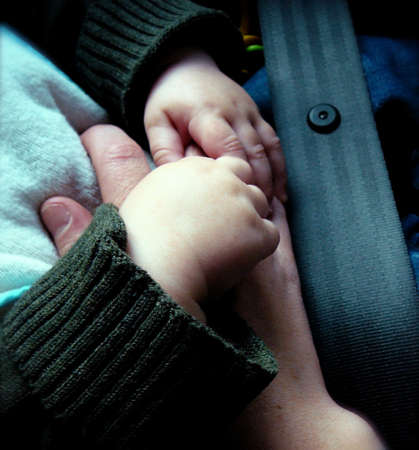 car seat: Detail of Hands:  Strapped into Car Seat with Seatbelt