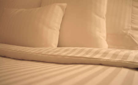 Detail of bed with set of crisp striped sheets and pillows Stock Photo