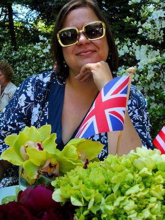 Beautiful young woman in large sunglasses posing in garden with British flag