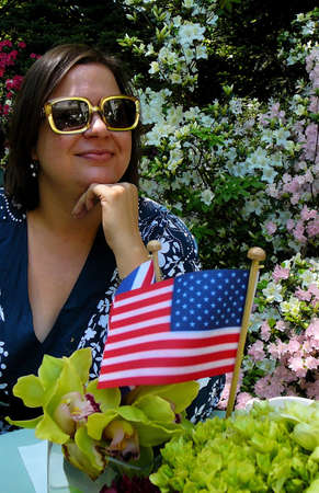 Beautiful young woman in large sunglasses posing in garden with American flag