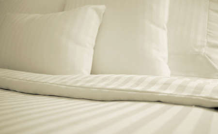 Detail of bed with set of crisp white striped sheets and pillows