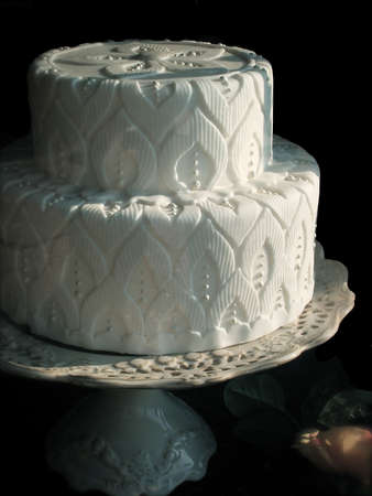 dessert stand: Elaborate White Wedding Cake on Cake Stand Isolated Over Black Background Stock Photo
