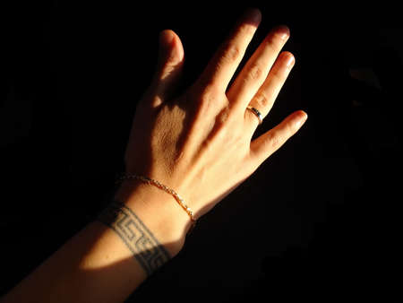 tattoo arm:  Hand with Greek Key Wrist Tattoo Gold Bracelet and Ring Isolated Over Black Background Stock Photo