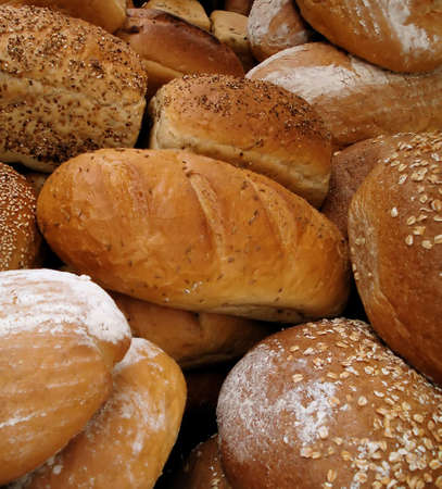 Variety of Fresh Baked Loaves of Gourmet Bread in Bakery Stock Photo