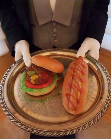 Butler in White Gloves and Elegant Silver Tray Serving Hamburger and Hot Dog at Summer Barbecue photo