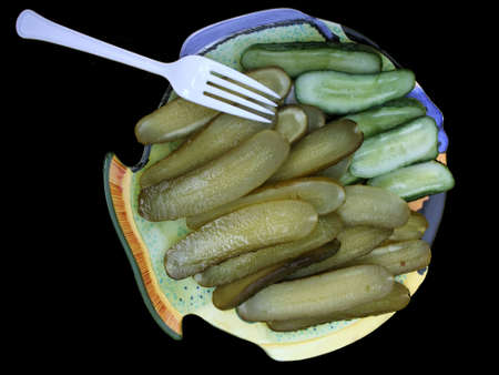 Sour Pickles Isolated Over Black Background photo