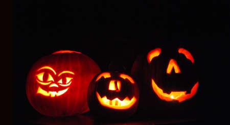 Trio of Spooky Carved Halloween Pumpkins Glowing in the Dark Night photo