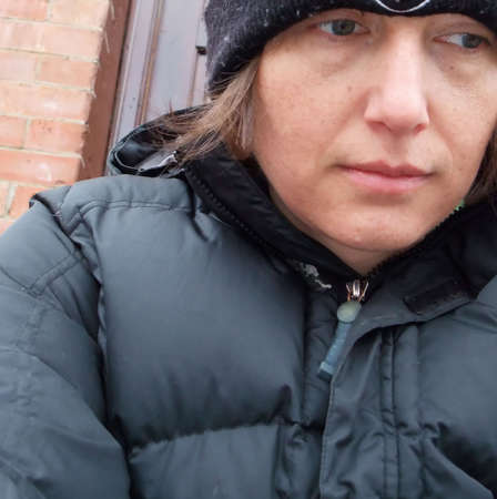 Closeup of woman wearing hat and down parka against the cold winter weather photo