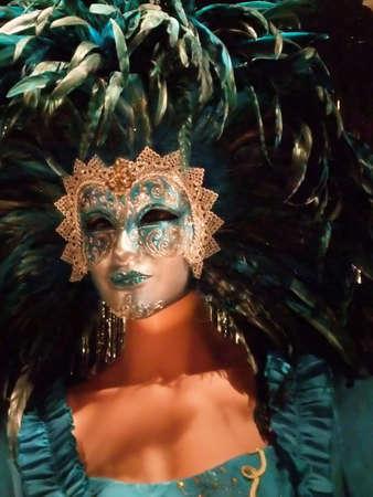 Vrouwelijke mannequin gekleed in gevederde maskerade masker en kostuum Stockfoto
