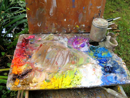 Painter Palette with Stains of Oil Paint on Easel photo