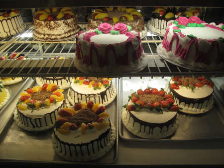 window display: Variety of Colorful Cakes in Bakery Window Display        Stock Photo