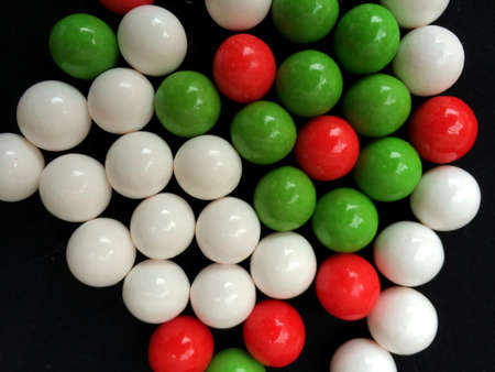 gumballs: Red, Green, and White Round Christmas Holiday Candy or Gumballs Isolated over Black Background Stock Photo