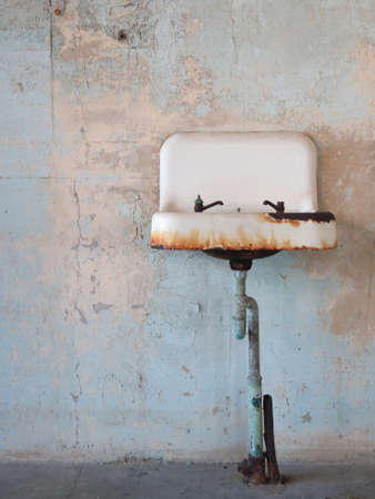 Rust covered ceramic old sink in abandoned bathroom photo