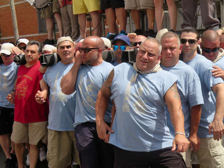 steel tower: Traditional Italian Giglio Parade 113th anniversary Catholic Parade, Williamsburg, Brooklyn, 2016: men carry one-ton steel tower from Our Lady of Mount Carmel Parish