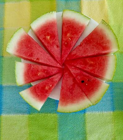 Organic seasonal summer watermelon sliced on tablecloth Stock Photo