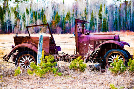 barb wire: Classic car next to barb wire fence
