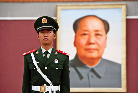 ze: Policeman being watched by portrait of chairman Mao Editorial