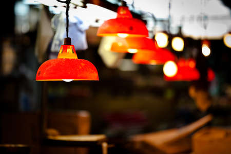 classic light bulb: Row of bright, red lights at a night market