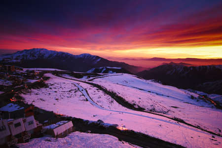 Fiery skies and pink snow during sunset in the Chilean Andes photo