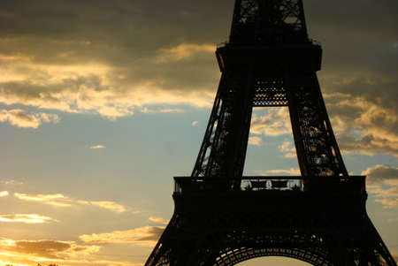 d'eiffel: Silhouette of the Eiffel Tower contrasts with beautiful sunlit clouds