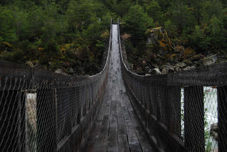 linking together: Hanging wooden bridge in the middle of a forest in Patagonia