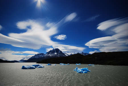 silently: Icebergs float silently under dramatic blue skies with clouds shaped by the wind in Torres del Paine national park Stock Photo