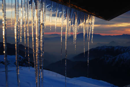 disappears: Icicles hanging from cabin roof light up as the sun disappears in the horizon of the Andean mountain range Stock Photo