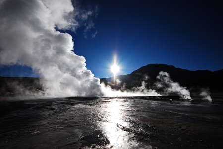 atacama: Sunlight is reflected on the water left by a geyser early in the morning Stock Photo