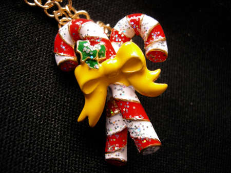 sugarplum:    Christmas sugar candy with bow and gold chain on a black background