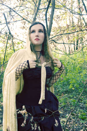 Wonderful medieval girl in a black dress and gold cloak.Or Enchantress at the Woodland at the day before . photo