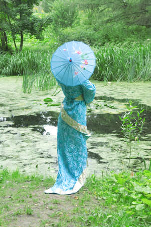 ultramarine blue: Lovely geisha in turquoise blue kimono with sky-blue parasol near the woodland pond.